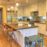 beachy kitchen with darn quartz and blue stacked tile back splash white shaker cabinets