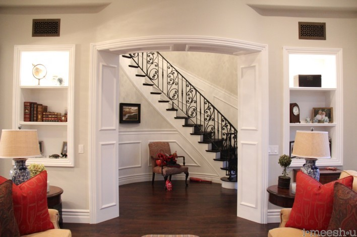 view of gorgeous sweeping wrought iron stairwell, white wainscoting panels