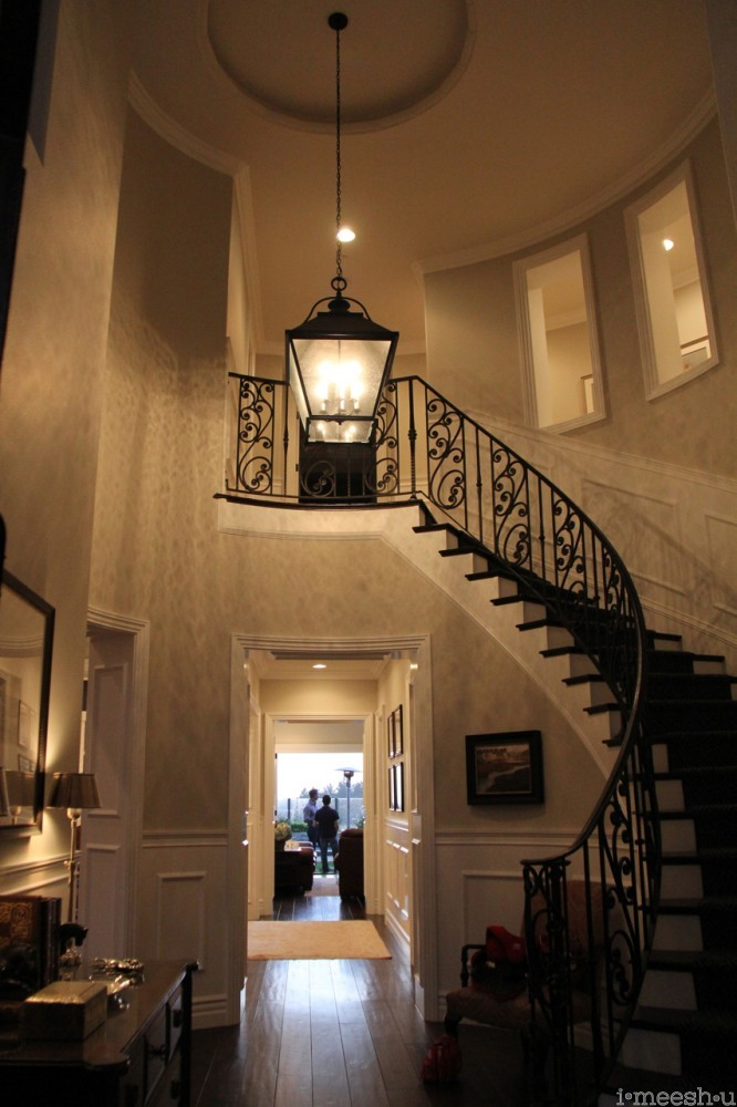 grandiose front entry sweeping curved wrought iron staircase