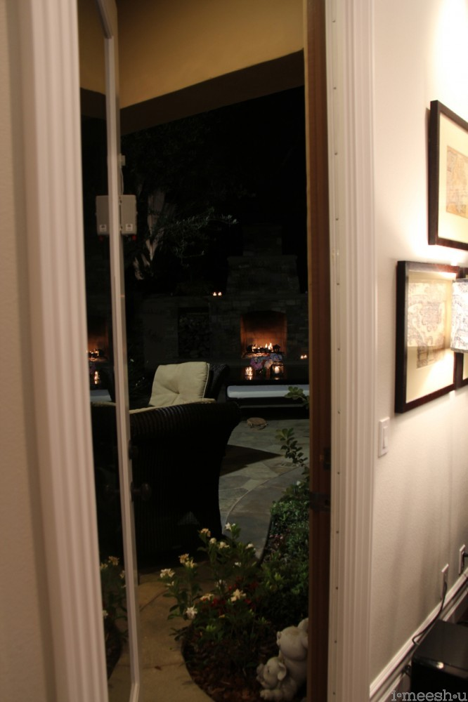 glimpse of outdoor fireplace from home interior