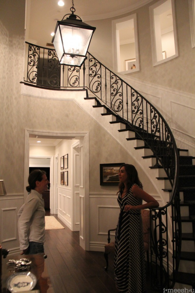 sweeping curved wrought iron stairwell white paneling