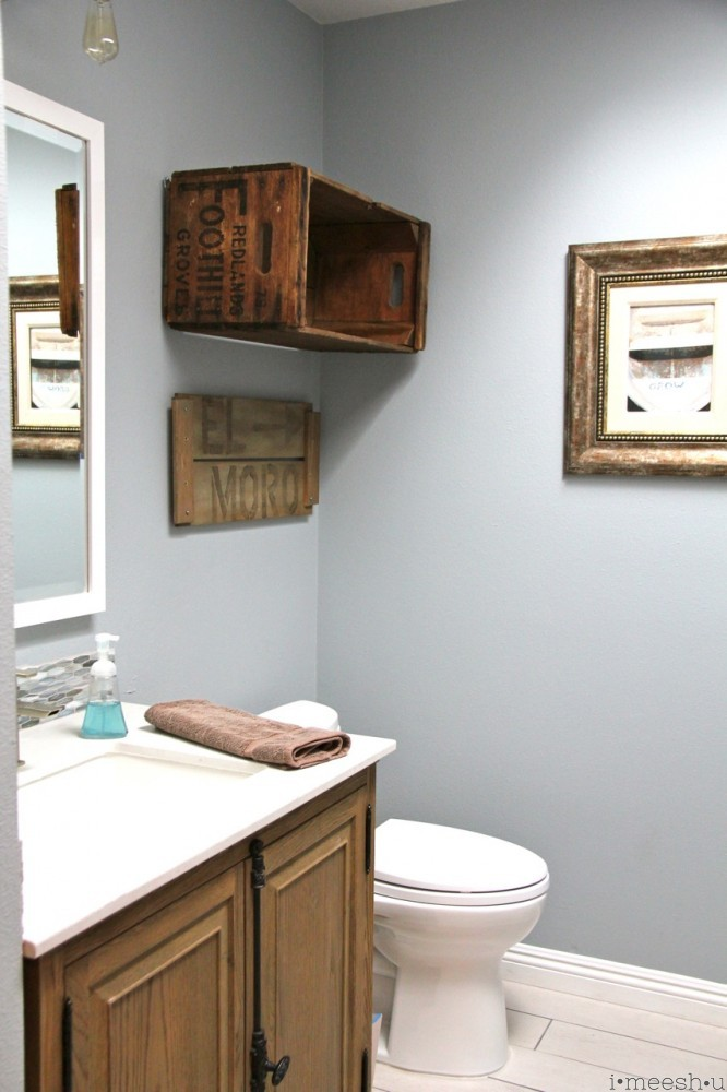 toilet with rustic wood crate to hold towels